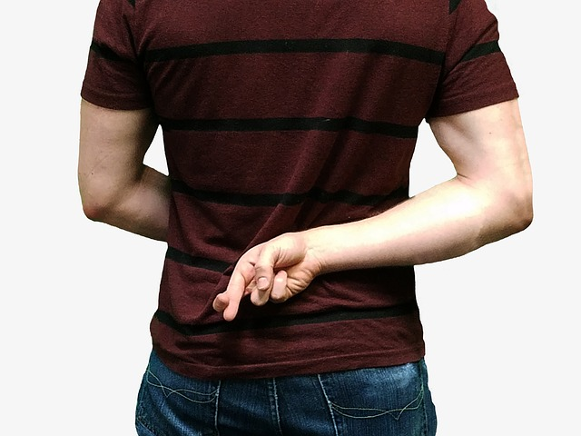 A man holding crossed fingers behind his back, showing that he is being dishonest.