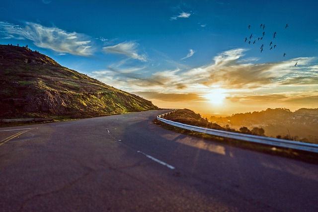 A winding road that curves away into a bright sunrise, with wispy clouds and birds in the sky.