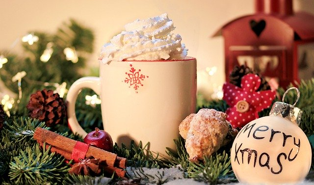 A cup of hot chocolate with shipped cream, nestled into a snowy pine bough with cinnamon sticks, lights, and ornaments.