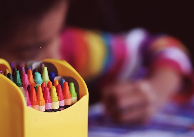 A close up of an open box of crayons, with an out-of-focus young child coloring at a desk in the background.