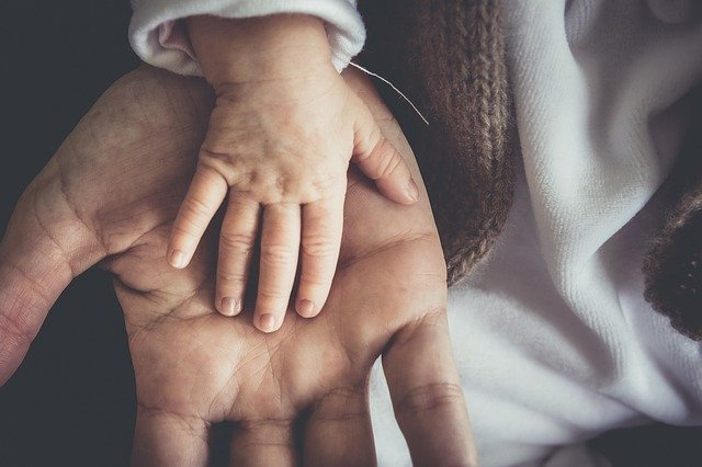 A father's open hand with a small child's hand lying across his palm.