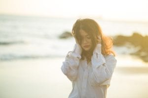 A young woman looking sad walking on a beach